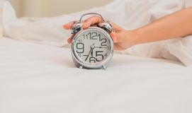Woman hand on alarm clock, Wake up concept. White bed background. stock image