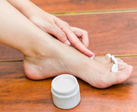 Woman hand applying moisturizer in her feet, best way to hydrate the skin Royalty Free Stock Photo