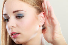 Woman with hand behind ear spying. Closeup female hand to ear listening on gray. Gossip girl with palm behind ear spying. Young woman listening secret royalty free stock photo