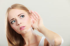 Woman with hand behind ear spying. Closeup female hand to ear listening on gray. Gossip girl with palm behind ear spying. Young woman listening secret stock photos