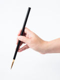 Woman hand and black brush. On white background Royalty Free Stock Photography