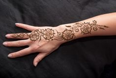 Picture of human hand being decorated with henna. Woman hand with black cute henna mehendi designs royalty free stock images