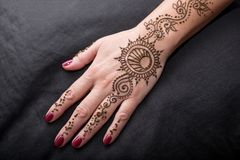 Picture of human hand being decorated with henna. Woman hand with black cute henna mehendi designs royalty free stock image