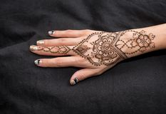 Picture of human hand being decorated with henna. Woman Hand with black cute henna mehendi designs royalty free stock photos