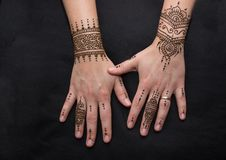 Picture of human hand being decorated with henna. Woman hand with black cute henna mehendi designs stock images