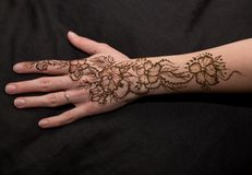 Picture of human hand being decorated with henna. Woman hand with black cute henna mehendi designs stock photo