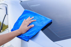 Woman hand with blue microfiber cloth cleaning the car Royalty Free Stock Photo