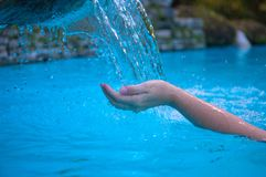 Woman hand and blue water. Cool water stream and hands. Fresh water current. Woman hands in clean flow. royalty free stock photos