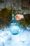 Woman hand with bottle at a beautiful frozen winter spring. Stock Photography