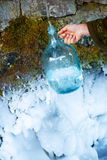 Woman hand with bottle at a beautiful frozen winter spring. Royalty Free Stock Photo