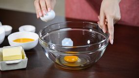 Woman hand breaks chicken egg in bowl. Chicken egg falls into glass bowl.