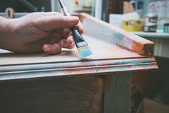Woman hand with brush paint wooden desk with chalky paint Royalty Free Stock Image