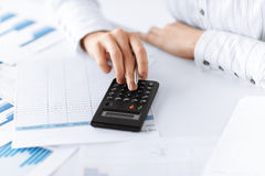 Woman hand with calculator and papers Royalty Free Stock Images