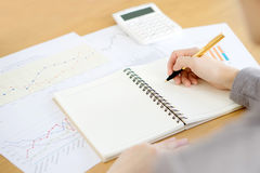 Woman hand with calculator and papers Royalty Free Stock Photo