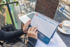 Woman hand carrying calendar and pointing on meeting day by pen royalty free stock photos