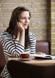 Woman With Hand On Chin Looking Away In Coffeeshop Royalty Free Stock Photos