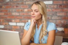 Woman with hand on chin looking at laptop Stock Images