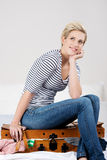 Woman With Hand On Chin Sitting On Overloaded Baggage Royalty Free Stock Photos