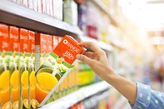 Woman hand choosing to buy orange juice on shelves in supermarket.  stock photos