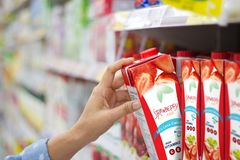 Woman hand choosing to buy strawberry juice on shelves in superm. Arket Royalty Free Stock Images