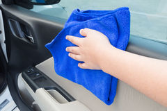 Woman hand cleaning interior car door panel with microfiber clot Royalty Free Stock Photos