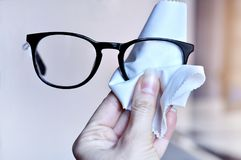 Woman hand cleaning trendy black glasses lens with white microfiber tissue. blur background. Royalty Free Stock Photos