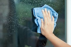 Woman hand cleaning window stock photos