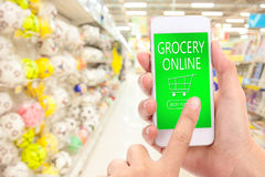 Woman hand click BUY NOW on mobile with blur supermarket background, Grocery online, delivery concept. stock photo
