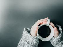 Woman hand with cloth hold the black coffee in white cup on morn Stock Image