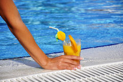 Woman hand with cocktail at swimming pool summer Stock Image