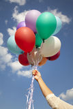 Woman hand with colorful balloons Stock Photo