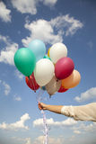 Woman hand with colorful balloons Stock Photography