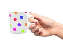 Woman hand with colorful polka dot cup of coffee Royalty Free Stock Images