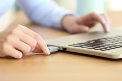 Woman hand connecting a pendrive in a laptop. Close up of a woman hand connecting a pendrive in a laptop on a desktop stock image