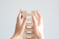 Woman hand constructing a tower of wooden blocks on a white background Stock Photography
