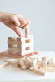Woman hand constructing a tower of wooden blocks on a white background Royalty Free Stock Image