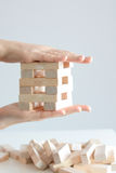 Woman hand constructing a tower of wooden blocks on a white background Stock Photo