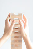Woman hand constructing a tower of wooden blocks on a white background Stock Image
