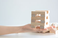 Woman hand constructing a tower of wooden blocks on a white background Royalty Free Stock Photos