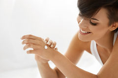 Woman Hand Cream. Close Up Of Beautiful Girl Applying Lotion Royalty Free Stock Photos