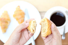 A woman hand with a cup of black coffee and a freshly baked cro Royalty Free Stock Image