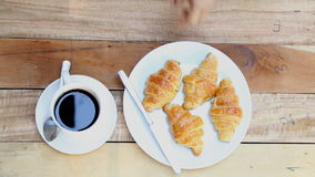 Woman hand with a cup of black coffee and a freshly baked croissant stock footage