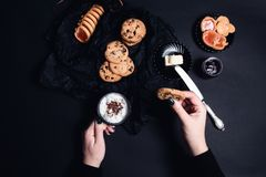 Woman hand with cup of coffee or cappuccino and chocolate cookies, biscuits on black table background. Afternoon break time. Break Royalty Free Stock Photo