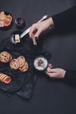 Woman hand with cup of coffee or cappuccino and chocolate cookies, biscuits on black table background. Afternoon break time. Break Stock Image