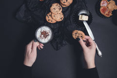 Woman hand with cup of coffee or cappuccino and chocolate cookies, biscuits on black table background. Afternoon break time. Break Stock Photography