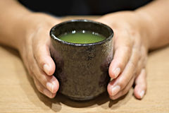 Woman hand with a cup of Green tea Royalty Free Stock Images