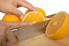 Woman hand cut orange in half Royalty Free Stock Photo