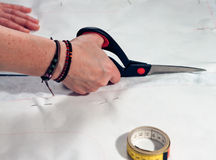 Woman hand cutting. Designer cutting fabric with a taylors scissors. Sewing pattern is secured to the fabric with pins. Rolled up measuring tape is lying on the Royalty Free Stock Images