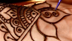 Woman hand decorated with henna tattoo, mehendi. On black background, close up, cam moves top down stock footage