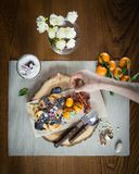 Woman hand decorates dish for breakfast on the stylish wooden tray royalty free stock images